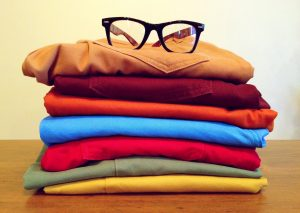 A pile of clothes with glasses resting on top