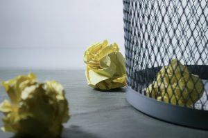 Yellow paper balls next to waste paper basket